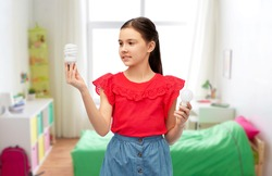 eco living and sustainability concept - smiling girl comparing energy saving light bulb with incandescent lamp over kids room background