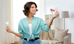 eco living, inspiration and sustainability concept - portrait of happy smiling young woman in turquoise shirt comparing energy saving light bulb with incandescent lamp over home room background