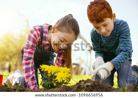 Eco project. Nice delighted children planting flowers while volunteering in the ecological project #1096656956
