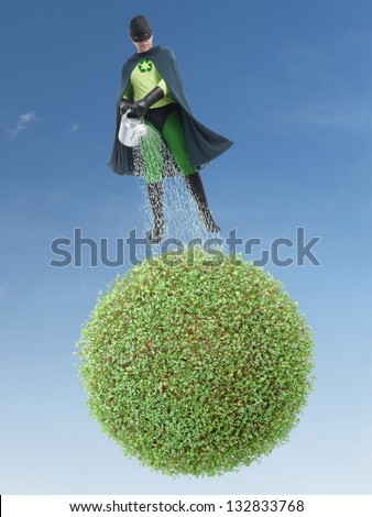 Eco superhero watering green planet from above - green environment concept