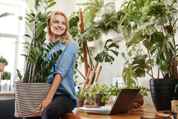 Ecofriendly businesswoman furnishing her place of work with houseplant