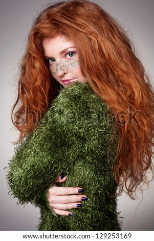 ecoist young ginger lady with green freckles on her face looking at camera