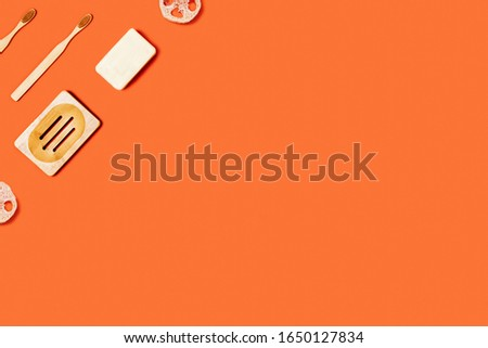 Ecological accessories for body care: natural sponges, soap, toothbrushes located on orange background.