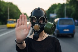 Ecological concept of air contamination. Woman in gas mask near highway showing stop gesture