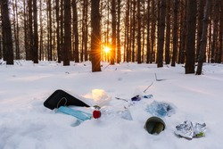 Ecological crisis. Different garbage and trash on snow at beautiful winter forest at bright sunrise with sunbeams through trees. Environmental pollution by garbage. Destructive human influence on