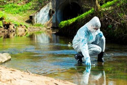 ecological disaster, contaminated water comes out of the sewage system - an ecologist takes a sample of water for research