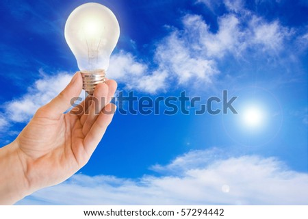 Ecological energy. Hand holds a light bulb against blue sky.