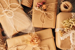 Ecological gifts wrapping in use. Eco materials for decorating presents: beige paper, dry flowers, skeleton leaves, lace and twine. Present boxes in florist rustic romantic style for Valentine's Day.
