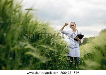 Ecologist in a white coat and glasses examining plants.