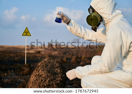 Ecologist in suit, gas mask holding test tube with blue liquid while studying burnt grass and soil on scorched territory with biohazard sign. Environmentalist doing laboratory test in field after fire Stock foto ©