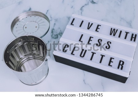ecology and consumerism concept: live with less clutter message on lightbox with open empty trash bin