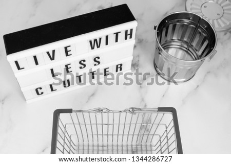 ecology and consumerism concept: live with less clutter message on lightbox with shopping basket and trash bin