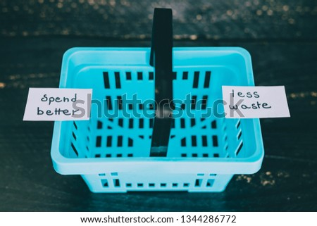ecology and consumerism concept: spend better for less waste empty shopping basket with text