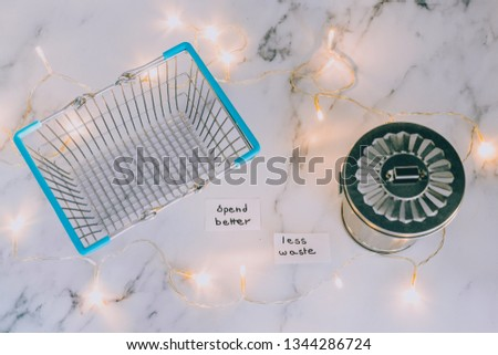 ecology and consumerism concept: spend better for less waste shopping basket next to gargabe bin and fairy lights on marble desk