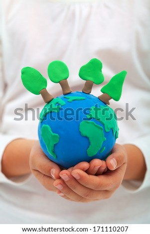Ecology and environment concept with trees on clay world in child hands