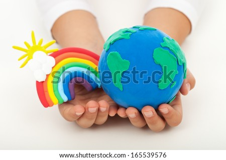 Ecology concept - a clean earth in child hands with colorful rainbow made of clay