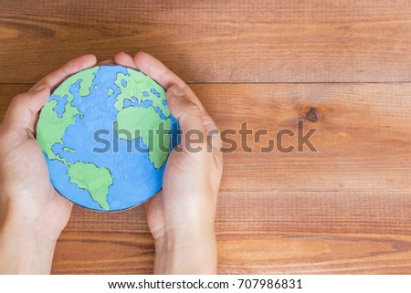 Ecology concept, holding a paper globe map painted blue and green, wooden background.  #707986831