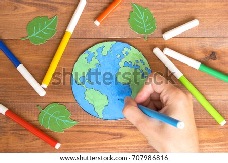 Ecology concept, painting a paper globe map blue and green, wooden background.  #707986816
