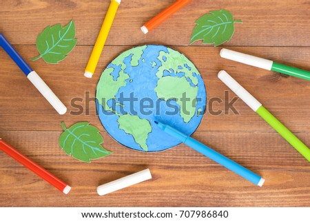 Ecology concept, painting a paper globe map blue and green, wooden background.  #707986840