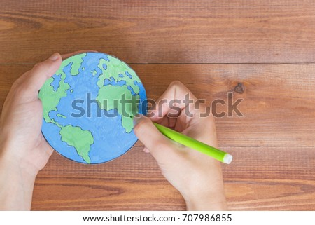 Ecology concept, painting a paper globe map blue and green, wooden background.  #707986855