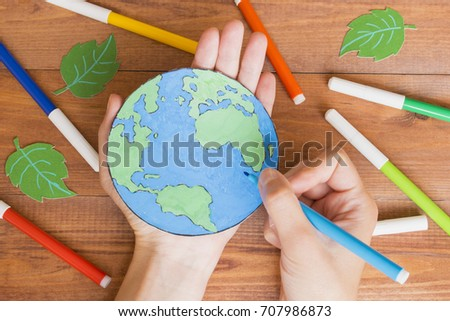 Ecology concept, painting a paper globe map blue and green, wooden background.  #707986873
