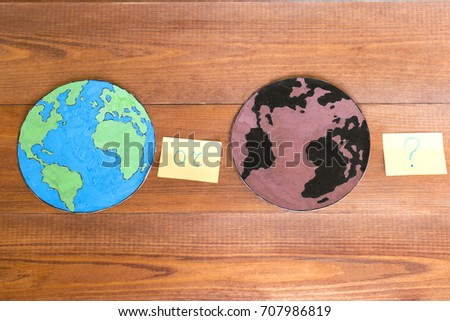Ecology concept, paper globe map painted blue and green and another painted black and brown, wooden background.  #707986819