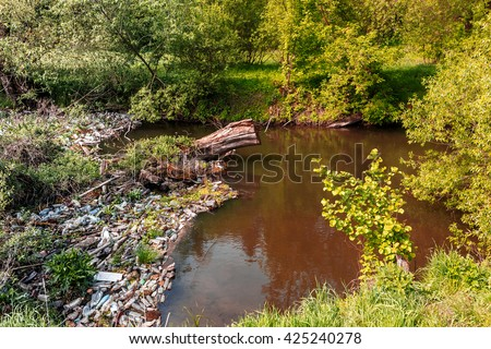 ecology concept. small river, water pollution, empty plastic bottles. River that is polluted with various garbage and trash, Polluted rivers,