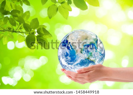 Ecology Concept : Woman hand holding planet earth globe with green natural in background. (Elements of this image furnished by NASA.) #1458449918