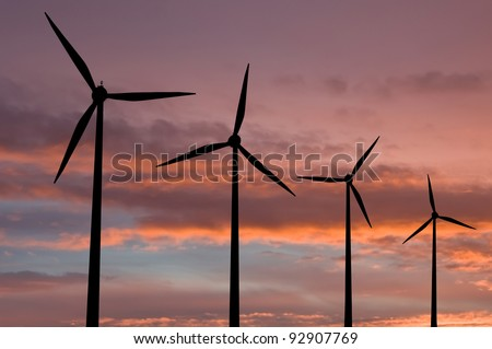Ecology electric energy farm with wind turbine at sunset