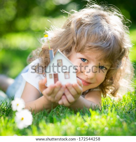 Ecology house in childrens hands against spring green background