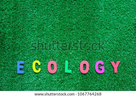 ECOLOGY wooden word on the plastic artificial green grass background for nature and environment concept #1067764268