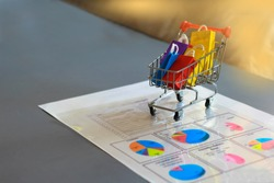 Ecommerce Shopping and Market Share Concepts: Putting Trolley on Report Paper in the Office.