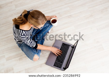 Ecommerce woman. Young female using computer for online shopping, sitting on the floor and drinking coffee.