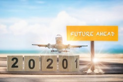Economic and business transportation recovery after covid-19 concept and happiness travel idea. 2020 to 2021 and commercial plane with future ahead word on wooden sign on tropical beach background