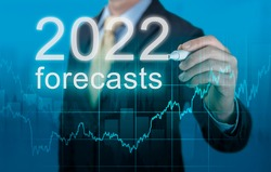 economic forecasts for 2022. businessman writes forecasts for 2022 on a virtual screen. Post covid-19 economic recovery. Businessman in suit forecast analysis plan profit chart with pen