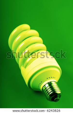 economic luminescent electric lamp on  green background,  close up