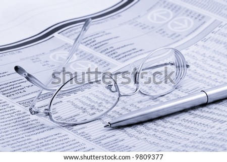 economic newspaper with glasses and pen