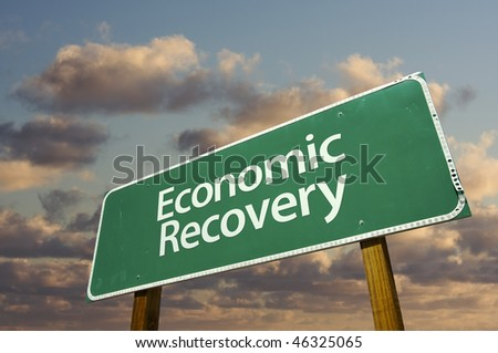 Economic Recovery Green Road Sign with dramatic clouds and sky.