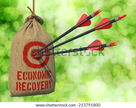 Economic Recovery - Three Arrows Hit in Red Target on a Hanging Sack on Green Bokeh Background.