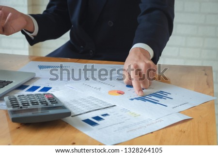 Economic research discussions, Business man discuss analyzing income charts and graphs to plan marketing concept with using laptop and calculator  for analysis. #1328264105