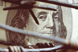 Economic warfare, sanctions and embargo busting concept Barbed wire against US Dollar bill. Close up.