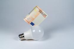 Economical light bulb and money (euros). Energy saving.