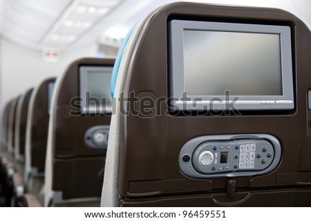 Economy class seats with entertainment system onboard a wide-body airliner. Shallow depth of field with the first seat in focus.