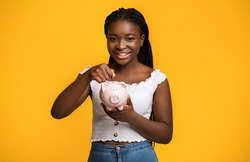 Economy Concept. Smiling Black Woman Holding And Inserting Coin At Piggy Bank, Saving Money For Future, Making Smart Investment, Positive Lady Standing Isolated Over Yellow Background, Copy Space
