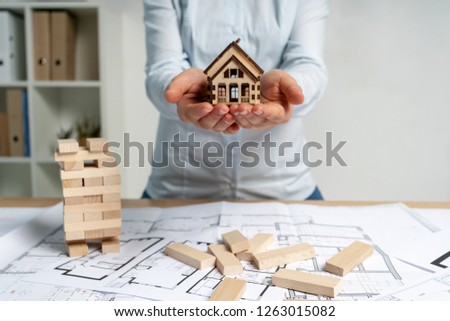 Economy tax, insurance risk, consumer and consumerism concept. Architect lady or broker manager in her formal wear stand inside workstation. She hold house in hand suggest credit for new building