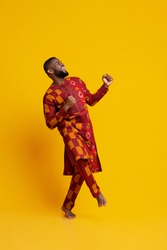 Ecstatic black man in traditional african clothes dancing over yellow studio background