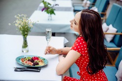 Ecstatic brunette girl chilling in cafe. Inspired young woman in red polka dot dress enjoying champagne in restaurant in summer weekend. Young woman sitting by table in restaurant.
