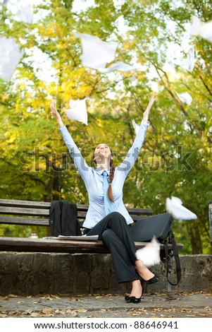 ecstatic businesswoman sitting on bench in park and  throwing paper in the air