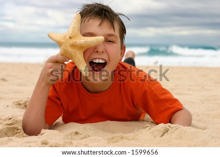 Ecstatic child lying on the beach holding a starfish to face.