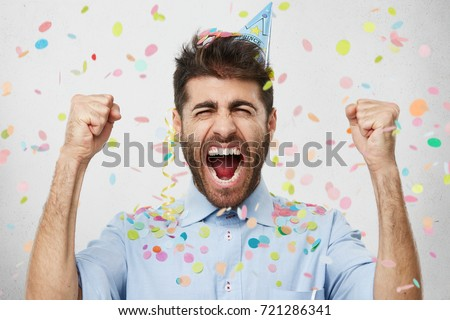 Ecstatic emotional young employee with thick beard wearing cone hat and formal shirt screaming in excitement, clenching fists, celebrating long awaited promotion at work with colleague at office